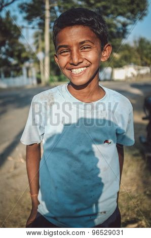 HAMPI, INDIA - 01 FEBRUARY 2015: Indian boy on street with photographers shadow on shirt. Post-processed with grain, texture and colour effect.