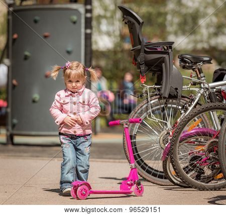 little girl with her scooter on a bicycle parking