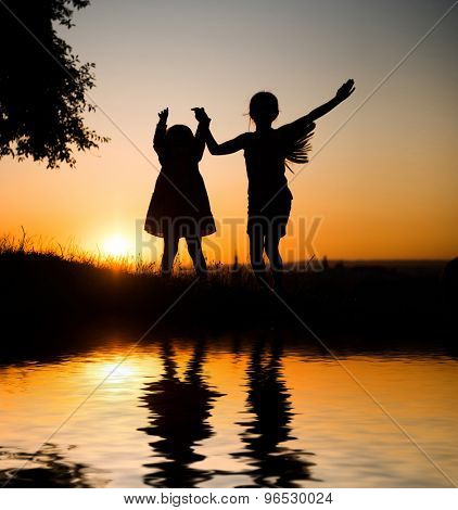 Silhouette of two young sisters on a background of beautiful sunset sky
