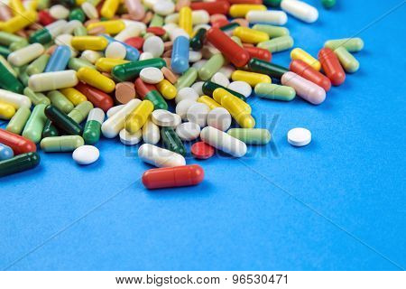 Lot Of Colorful Pills On A Blue Background