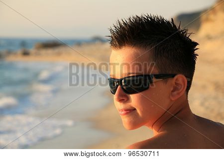 Portrait of young boy wearing sunglasses and posing by sea
