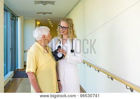 Happy Nurse Assisting Elderly At Hospital Corridor