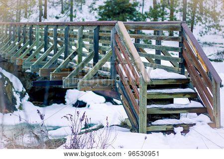 Rustic wooden bridge in snow