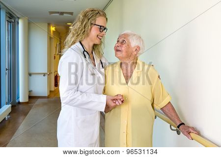 Medical Assistant Assisting Elderly In Hospital