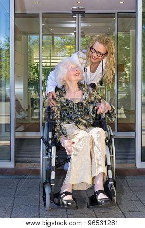 Kind Nurse Talking To Elderly Woman On Wheelchair