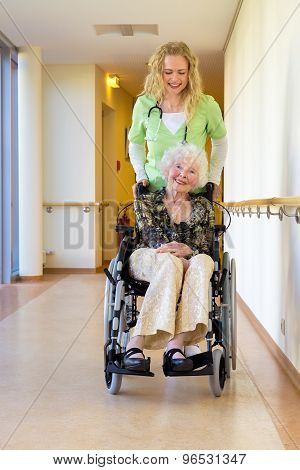 Nurse Assisting Elderly On Wheelchair At Corridor