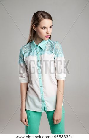 Attractive woman in white blouse and turquoise pants