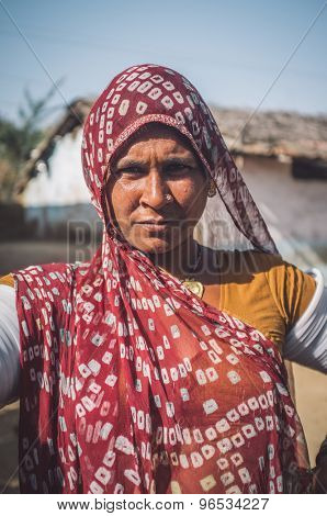GODWAR REGION, INDIA - 13 FEBRUARY 2015: Rabari tribeswoman in sari decorated with traditional upper-arm bracelets. Post-processed with grain, texture and colour effect.