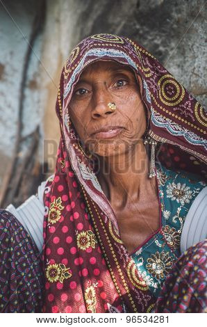 GODWAR REGION, INDIA - 13 FEBRUARY 2015: Rabari tribeswoman in sari decorated with traditional upper-arm bracelets and jewerelly. Post-processed with grain, texture and colour effect.