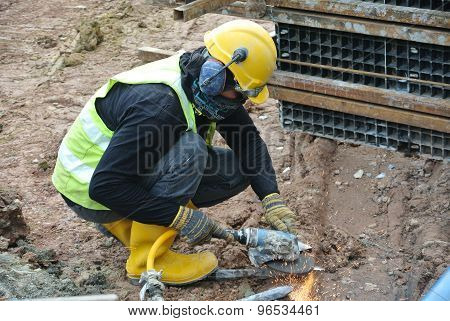 Construction workers using construction grinder to sharpen steel at construction site