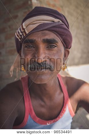 GODWAR REGION, INDIA - 14 FEBRUARY 2015: Mechanic with mustache wearing headscarf and big golden earings sits outside of workshop. Post-processed with grain, texture and colour effect.