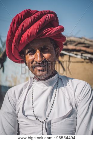 GODWAR REGION, INDIA - 13 FEBRUARY 2015: Rabari tribesman stands in courtyard of home wearing traditional clothes. Post-processed with grain, texture and colour effect.