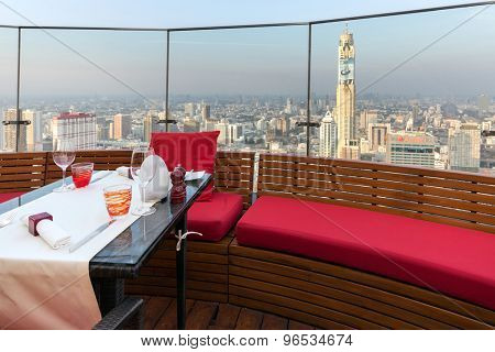 BANGKOK, THAILAND, JANUARY 14, 2015 : Restaurant table with view on the cityscape at the Red Sky Rooftop of the Centara hotel in Bangkok, Thailand.