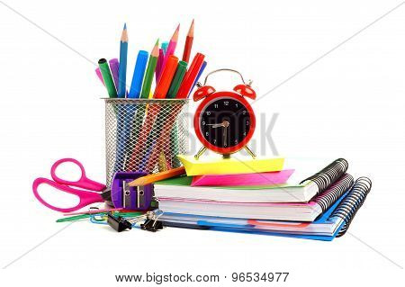 School supplies with alarm clock over white