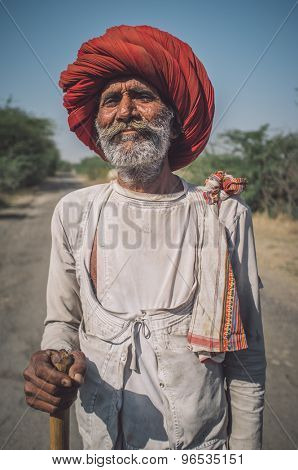 GODWAR REGION, INDIA - 14 FEBRUARY 2015: Elderly Rabari tribesman with big red turban and cane stands on road. Post-processed with grain, texture and colour effect.