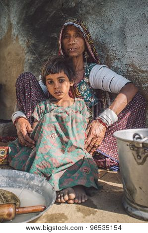 GODWAR REGION, INDIA - 13 FEBRUARY 2015: Rabari tribeswoman in sari decorated with traditional upper-arm bracelets holds granddaughter in dress. Post-processed with grain, texture and colour effect.