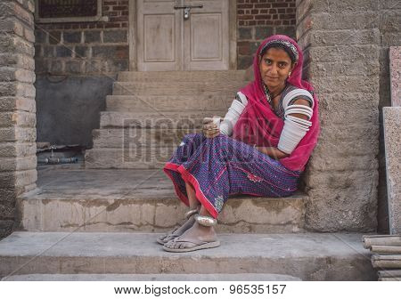 GODWAR REGION, INDIA - 15 FEBRUARY 2015: Indian tribeswoman sitting in front of home in saree decorated with upper-arm bracelets. Post-processed with grain, texture and colour effect.