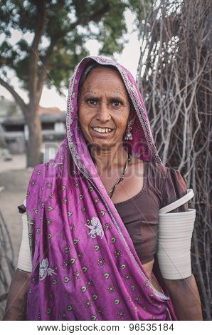 GODWAR REGION, INDIA - 12 FEBRUARY 2015: Tribeswoman decorated with traditional tattoos on face,  jewelry and upper arm bracelets. Post-processed with grain, texture and colour effect.