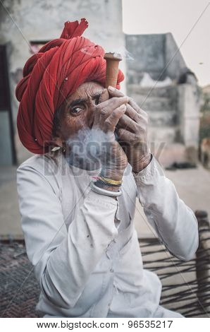 GODWAR REGION, INDIA - 12 FEBRUARY 2015: Rabari tribesman smokes chillum. Post-processed with grain, texture and colour effect.