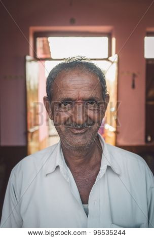 GODWAR REGION, INDIA - 12 FEBRUARY 2015: Elderly Indian man in home with door open in background. Post-processed with grain, texture and colour effect.