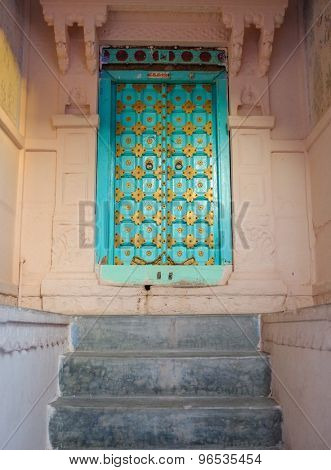 JODHPUR, INDIA - 07 FEBRUARY 2015: Entrance to home designed in typical style for Rajasthan region. Wooden door with carved details decorated with golden plates surrounded by carved stone walls.