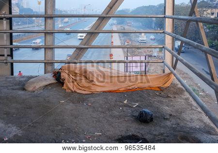MUMBAI, INDIA - 05 FEBRUARY 2015: Person sleeps on overpass on dirty ground with whole body covered under blanket. Common scene on India's streets.