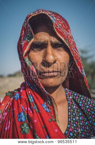 GODWAR REGION, INDIA - 14 FEBRUARY 2015: Rabari tribeswoman stands in field wearing saree. Post-processed with grain, texture and colour effect.