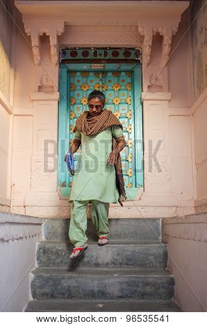 JODHPUR, INDIA - 07 FEBRUARY 2015: Woman in traditional clothes and scarf walking down stairs. Stone entrance and wooden door with gold panels are decorated in style typical to Rajasthan region.