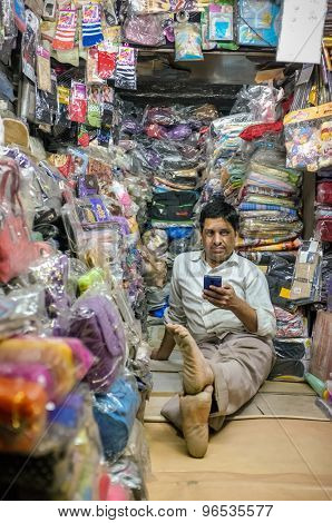 JODHPUR, INDIA - 07 FEBRUARY 2015: Store owner sitting on floor of clothing shop with mobile phone while waiting for customers. Little local textile shop overflown with different merchandise.