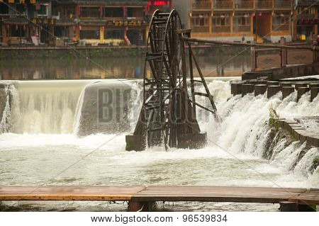 Wooden waterwheel on river in Fenghuang ancient city.