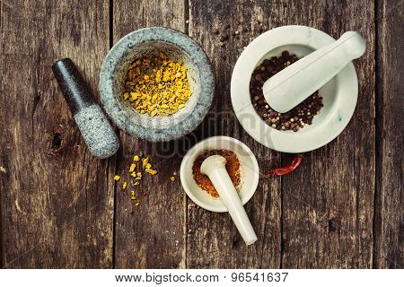Spices in a mortar on dark wood table