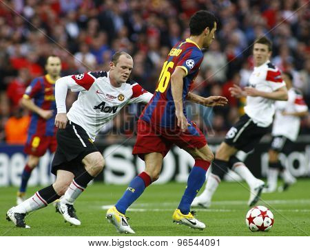 LONDON, ENGLAND. May 28 2011: Manchester's forward Wayne Rooney and Barcelona's midfielder Sergio Busquets during the 2011 UEFA Champions League final between Manchester United and FC Barcelona