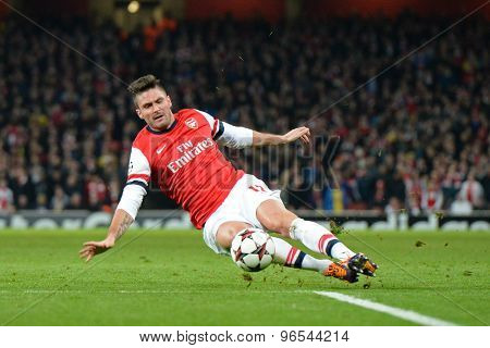 LONDON, ENGLAND - Nov 26 2013: Arsenal's Oliver Giroud slips as he takes a shot at goal during the UEFA Champions League match between Arsenal and Olympique de Marseille, at The Emirates Stadium