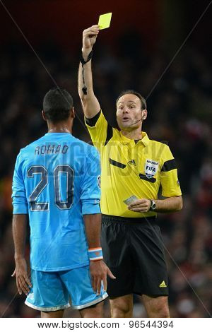 LONDON, ENGLAND - Nov 26 2013: referee Antonnio Miguel Mateu Lahoz shows a yellow card to Marseille's Alaixys Romao during the UEFA Champions League match between Arsenal and Olympique de Marseille