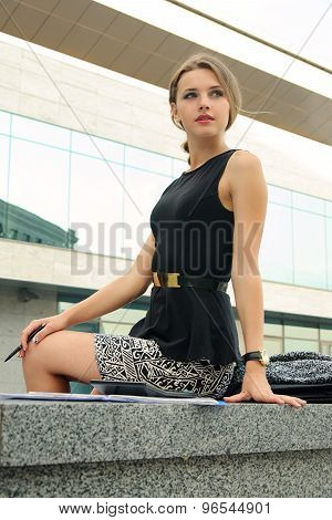 Business Woman Sitting On A Granite Parapet