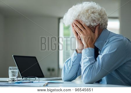 Exhausted Businessman With Head In Hands