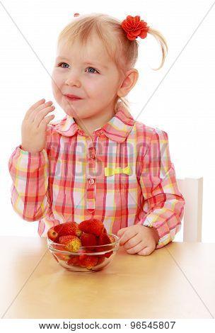 Little girl eating strawberries
