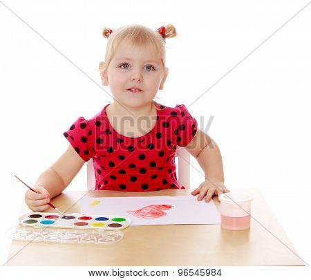 The girl draws with watercolors