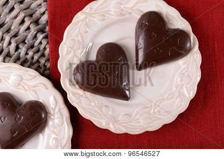 Chocolate heart shaped candies on sticks in white plate, closeup