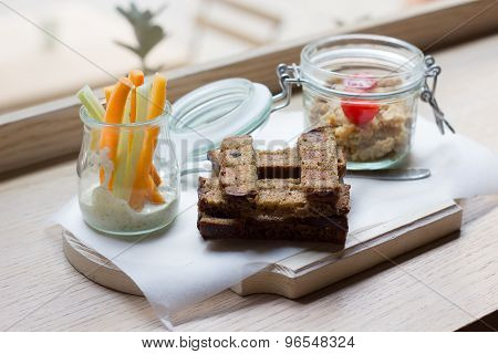 Hummus and bread on Wooden board. Carrots in a glass jar
