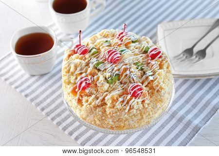 Butter cake with cherries on stand and table setting, on light background