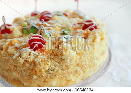 Butter cake with cherries on stand, on light background