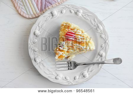 Peace of tasty Butter cake on plate, on color wooden background