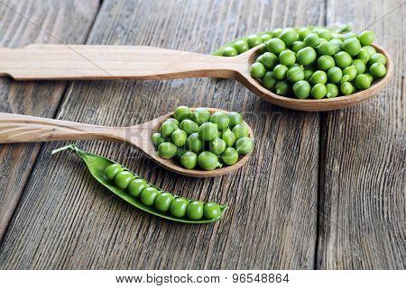 Fresh green peas in wooden spoon on table close up