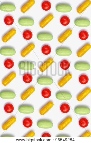 Many colored pills / capsules geometric pattern on white background