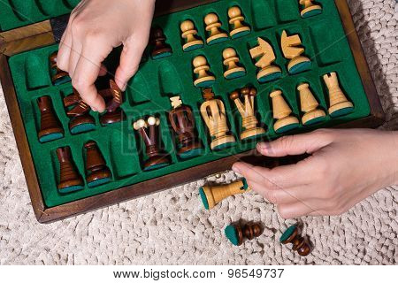 Hands Putting The Chess Pieces In Box After Game