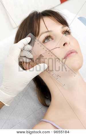 doctor preparing patient woman for facial plastic surgery