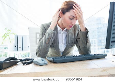 Upset young business woman sitting with head in hands in front of computer at office desk