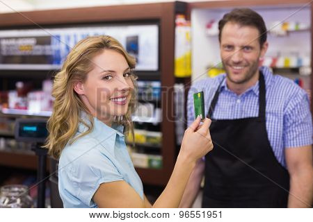 Woman at cash register paying with credit card in supermarket