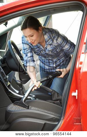 Woman Cleaning Inside Of Car Using Vacuum Cleaner